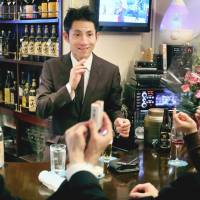 Another round: Deaf bartender Dai Igarashi attends to his customers at Bell Sign in Tokyo's Ginza district in April. | KYODO