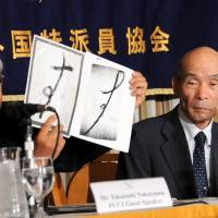 What similarity?: Lawyer Taketoshi Nakayama holds up a sample (right) of a 1963 ransom note linked to a kidnap-murder of a Saitama girl and the same hiragana character made by the man convicted in the slaying, Kazuo Ishikawa, who looks on during a Thursday news conference in Tokyo. | SATOKO KAWASAKI