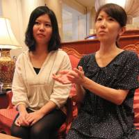 Hand in hand: Eriko Kajita (left), head of student group Namaste!, and her deputy, Aki Yasuda, recount their aid activities in India during a recent interview in Nagoya. | CHUNICHI SHIMBUN