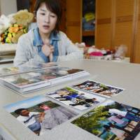 In the line of duty: Maya Momma shows pictures of her husband, Takafumi, a volunteer fireman claimed by the March 2011 tsunami in Minamisoma, Fukushima Prefecture, on April 30. | KYODO
