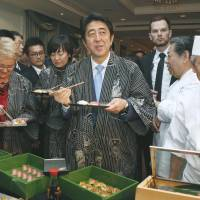 Taste of home: Prime Minister Shinzo Abe tucks into some sushi during a reception in Warsaw on Saturday to promote Japanese food, during his tour of Eastern Europe. | KYODO