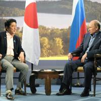 Side chat: Prime Minister Shinzo Abe and Russian President Vladimir Putin hold talks on the sidelines of the Group of Eight leaders' summit in Enniskillen, Northern Ireland, on Monday. | POOL