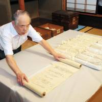 Ancient court life: Osamu Nawa, head of Yomei Bunko, a library in the city of Kyoto storing diaries of Fujiwara no Michinaga, shows the scrolls Wednesday. | KYODO