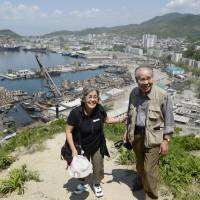 Revisiting: Takashi Fukushima, who used to live in Chongjin in what is now North Korea, and a fellow Japanese who also lived in the North, take in a vista point of the city Tuesday. | KYODO