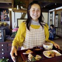 Working woman: Nabi  Togo serves meals using vegetables donated by neighbors and fish purchased nearby at a restaurant she operates in a refurbished home in Fukutsu, Fukuoka Prefecture, in April. | KYODO