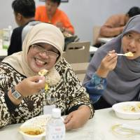 Dining at ease: Indonesian women eat halal meals purchased from Tokyo-based Halal Deli in Minato Ward on June 13. | KYODO