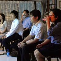 Emotional release: Participants at a 'rui-katsu' (tear-seeking) event watch a documentary on the March 2011 Tohoku disasters earlier this month in Atsuta Ward, Nagoya. | CHUNICHI SHIMBUN