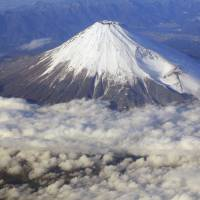 Snow cone: A snow-capped Mount Fuji is photographed from an airplane in December 2010. | AP
