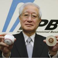Not the same: NPB commissioner Ryozo Kato, seen in a 2010 file photo, holds the ball that was introduced in 2011. | KYODO