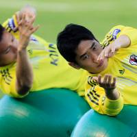 Reach for the stars: Shinji Kagawa (right) and Yuto Nagatomo exercise during a training session in Goma, Brazil, ahead of Saturday's Confederations Cup opener against Brazil. | AP