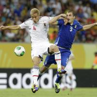 Tooth and nail: Keisuke Honda vies for the ball with Italy's Giorgio Chiellini in their Group A match at the Confederations Cup on Wednesday night in Recife, Brazil. Italy won 4-3 and eliminated Japan from the competition. | AP