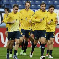 Party crashers: Members of the Australian national team jog during practice on Monday. | KYODO