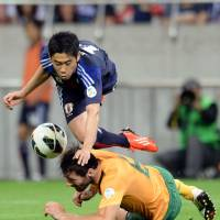 Brazil here we come: Japan's Shinji Kagawa (top) collides with Australia's Sasa Ognenovski during their 1-1 World Cup-qualifying draw in Saitama on Tuesday. | AFP-JIJI