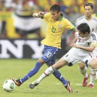 Hard to handle: Neymar (left) takes the ball away from Japan captain Makoto Hasebe during Brazil's 3-0 win on Saturday. | AP