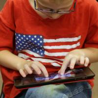 Finger-pointing: A second-grader uses an Apple iPad at Park Lane Elementary School in Sandy, Utah. | BLOOMBERG