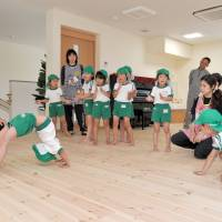 Children get guidance in how to do handstands in Byobugaura Harukaze's play hall. | YOSHIAKI MIURA