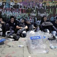 Exhausted  Turkish riot police rest the same day during the operation to clear the square, which has been the epicenter of nearly two weeks of anti-government protests. | AFP-JIJI