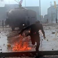 In the line of fire: A Turkish protester whose clothes are on fire runs away from riot police during clashes in Istanbul's Taksim Square on Tuesday. | AFP-JIJI