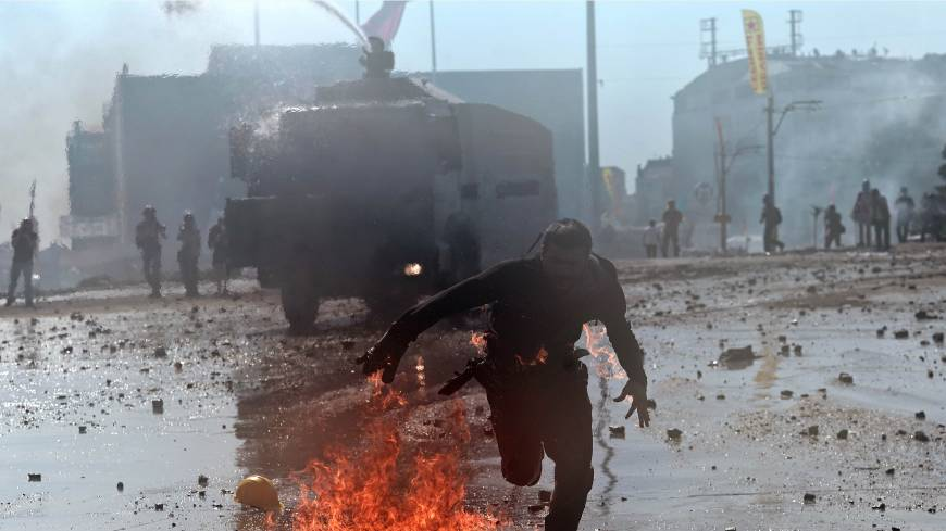 In the line of fire: A Turkish protester whose clothes are on fire runs away from riot police during clashes in Istanbul's Taksim Square on Tuesday.
