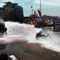 Fighting the power: A Turkish protester is hit by a water cannon during clashes with riot police in Istanbul's Taksim Square on Tuesday. Police later cleared the square and an uneasy calm had returned to the area as of Wednesday. | AFP-JIJI