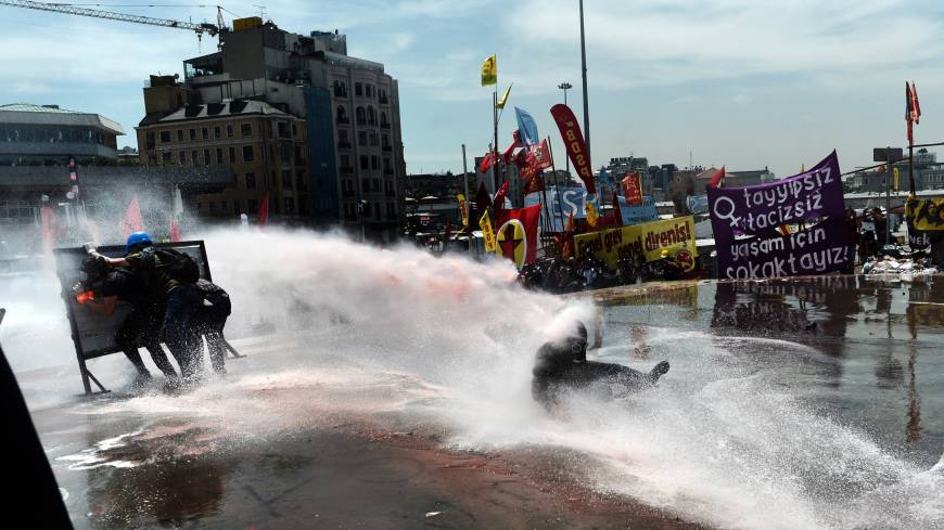 Fighting the power: A Turkish protester is hit by a water cannon during clashes with riot police in Istanbul's Taksim Square on Tuesday. Police later cleared the square and an uneasy calm had returned to the area as of Wednesday.