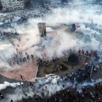 2020 Olympic bid in question: Protesters flee as Turkish riot police fire tear gas in Taksim Square on Wednesday. | AFP-JIJI