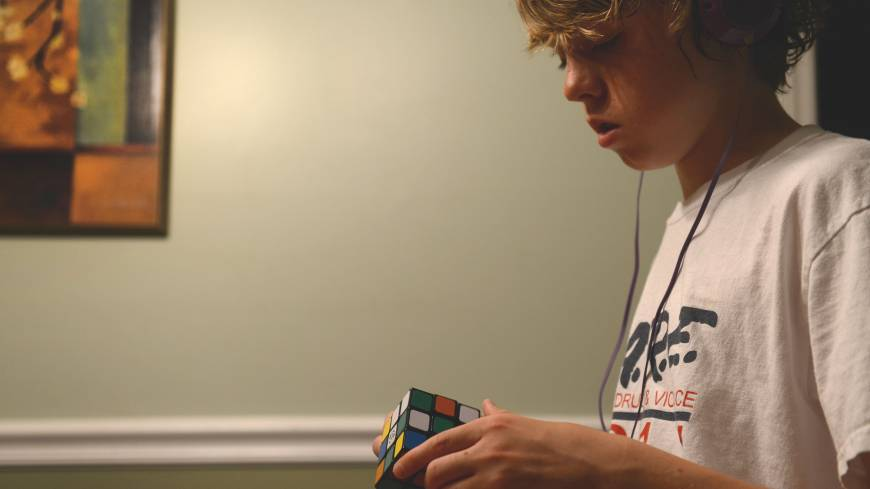James Barden, 13, listens to music while working on a Rubick's Cube at home.