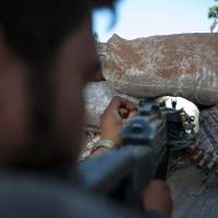 Under the gun: A Syrian rebel fighter points his rifle through a hole in sandbags as he holds a position in a trench 100 meters from the regime-controlled Wadi Deif military base in the village of Kfarruma on Friday. | AFP-JIJI