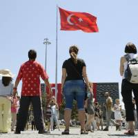 Taking a stance: Protesters stand silently as they stare at Turkey's national flag in Istanbul's  Taksim Square. Inspired by the actions of Erdem Gunduz, the stance has been adopted as a new way to get the demonstrators' message across. | KYODO