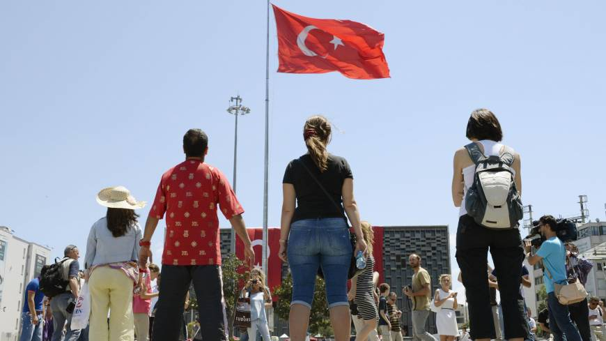 Taking a stance: Protesters stand silently as they stare at Turkey's national flag in Istanbul's  Taksim Square. Inspired by the actions of Erdem Gunduz, the stance has been adopted as a new way to get the demonstrators' message across.