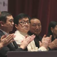 Sheep mentality?: Actor Jackie Chan claps with other Chinese delegates  Tuesday at the opening of a film festival in New Delhi. New research shows that individuals feel pressure to join people clapping, even if they don't agree with the sentiment. | AP