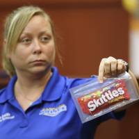 Food for thought: A crime scene technician for the Sanford Police Department holds up a bag of Skittles candy that was collected as evidence at George Zimmerman's trial in Sanford, Florida, on Tuesday. | AP