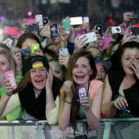 On record: Fans of Canadian singer Justin Bieber hold up mobile phones to take photographs and video of his concert at Telenor Arena in Fornebu, Norway, in April 2013. | AFP-JIJI