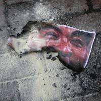 Under fire: A charred picture of Hong Kong Chief Executive Leung Chun-ying lies on the ground following a flag raising ceremony Monday to mark the 16th anniversary of the handover of the former British territory to China. | AP