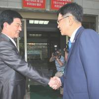 Shake on it: Suh Ho (right), head of a South Korean working-level delegation attending inter-Korean talks, shakes hands with his North Korean counterpart, Park Chol Su, on the North Korean side of the truce village of Panmunjom on Saturday. | AFP-JIJI