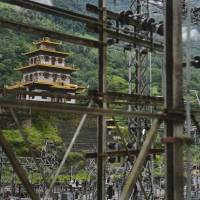 Switched on: A Buddhist temple stands behind pylons and other infrastructure at the Chukha hydropower station in southeast Bhutan in May. The sleepy kingdom is eyeing becoming an energy powerhouse thanks to its abundant water supply. | AFP-JIJI