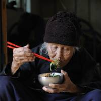 Fine dining:  An elderly woman in southern China's Hainan province eats freshly prepared vegetables for her lunch, while at the same time keeping illnesses at bay. | AFP-JIJI