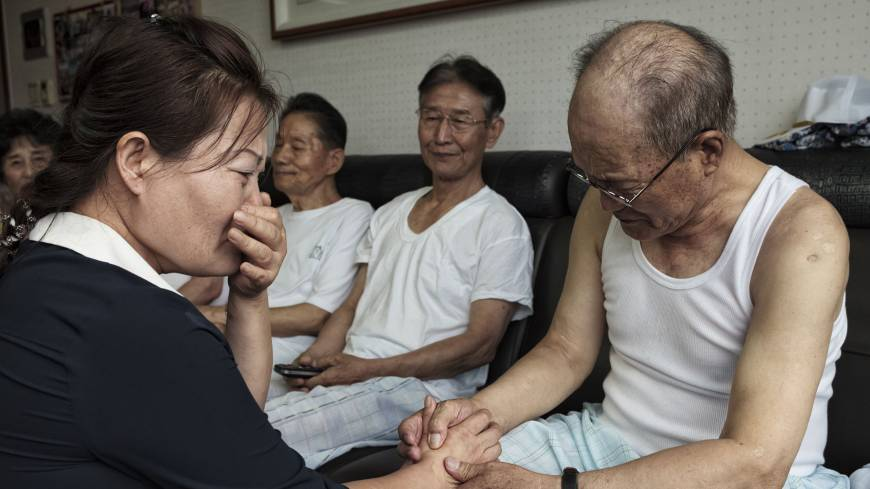 Second lives: Kim Kyung-hee, 40, bursts into tears as she speaks with Lee Sun-woo, 82, on Wednesday in Seoul. Lee was captured by Chinese troops during the Korean War in July 1953, 13 days before the armistice was signed, and detained as a prisoner to work in a coal mine until he escaped from North Korea in 2006. Kim escaped from North Korea in 2012; her late father, Kim Woo-yong, worked in the same coal mine as Lee from 1953 to 2004.