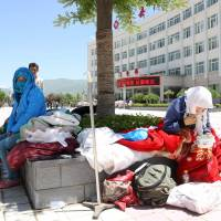 Seeking help: People wait outside Min County Hospital for treatment after a pair of strong earthquakes hit northwestern China's Gansu province early Tuesday. | AFP-JIJI