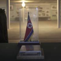Us and them: A North Korean soldier walks past a display of the armistice agreement between the two Koreas at the truce village of Panmunjom in the demilitarized zone on Monday.   AP