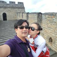 Travel for two: Fan Yue, deputy director of policy and regulation under the State Archives Administration, takes a photograph of himself and his mistress, Ji Yingnan, at the Great Wall of China. | THE WASHINGTON POST