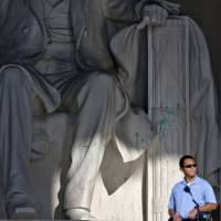 Dastardly act: A U.S. police officer stands guard at the Lincoln Memorial in Washington on Friday after a vandal splattered green paint on the statue and the floor area. | AP