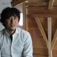 Crossing boundaries: Takashi Kuribayashi (aboce), sitting in front of one of his yatai portable food stalls, talks about his work, and Tokujin Yoshioka peers through his 'Waterfall' made of optical glass. | DANIELLE DEMETRIOU