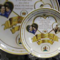 Serving up a profit: Souvenir plates that mark the forthcoming birth of Prince William and Kate, Duchess of Cambridge's baby are seen on display in a shop in central London. | AP