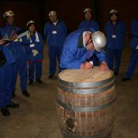 Sign of hope: Higashi-Matsushima folk look on as I inscribe their 'My Whisky' barrel. | PHOTO COURTESY OF NIKKA WHISKY, SENDAI