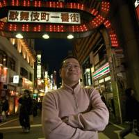 Gates from hell: Hidemori Gen stands in front of the entrace of Kabukicho in Shinjuku. Gen's 'Japan Social Minority Center' an NPO rescue center, is located within. | WILL ROBB PHOTO