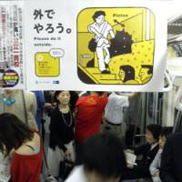 Wet-nursing: A poster in a train carriage urges Tokyo subway riders to 'be careful when handling a wet umbrella.' | BRETT BULL