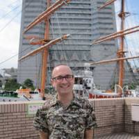 Writing full-time: Jon Mitchell stands among the landmarks of his adopted city, Yokohama. | KRIS KOSAKA