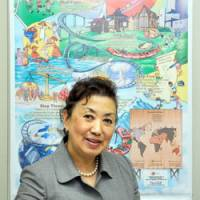 Global mind-set: Ikuko Atsumi poses in front of a learning map for students, titled '10 Steps to Reach the Global Village.' | SATOKO KAWASAKI PHOTO