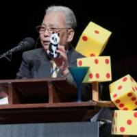Unwasted words: Holding a cardboard cutout of a giant panda, and with his double-dice award trophy at his elbow, Fumiaki Taguchi delivers his brief Ig Nobel Prize acceptance speech during the Oct. 1 ceremony at Harvard University. | FUMIAKI TAGUCHI
